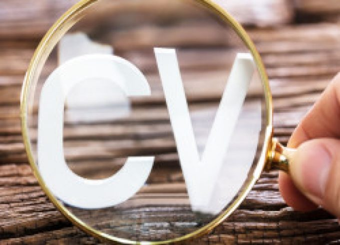 A Person Looking At White CV Word Through Magnifying Glass