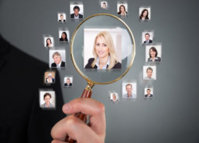 Cropped image of businessman searching candidate with magnifying glass over gray background